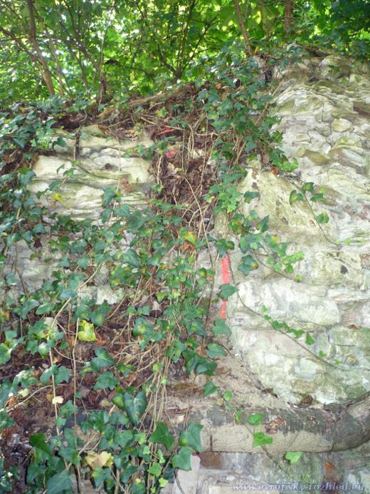 Sprejem vyznačená značka na ruinách starého domu nebo zídky.