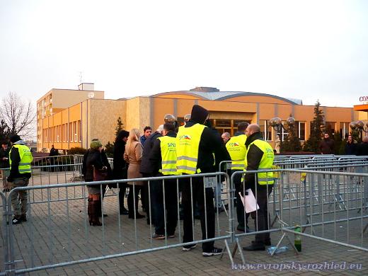 Muži v reflexních vestách SPD Tomia Okamury střeží vstup do hotelu.