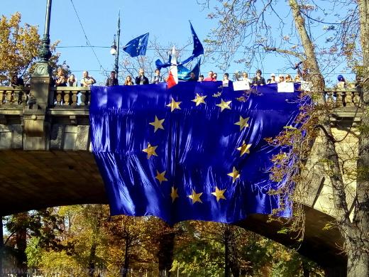 Přesun s několikametrovou vlajkou Evropské unie přes most Legií.