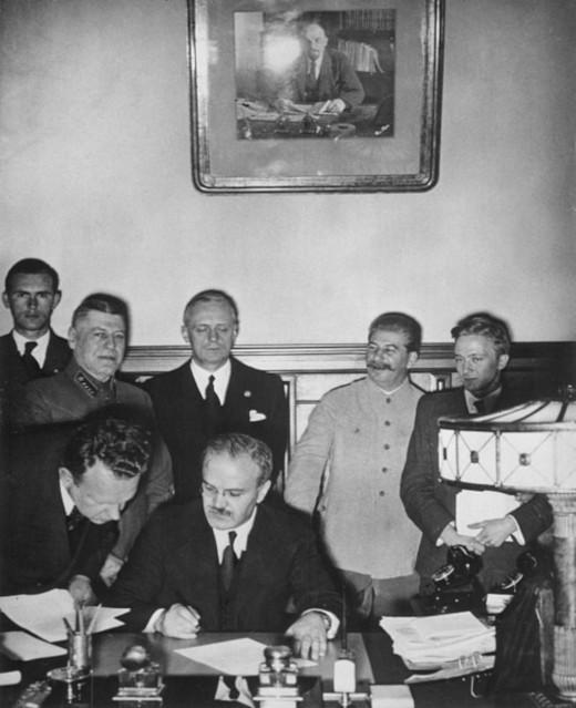 Molotov podepisuje německo-sovětskou smlouvu o neútočení. Za ním je vidět Ribbentrop (v černém) a Stalin (ve světlém, druhý zprava) - zdroj: Wikipedie