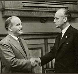 Molotov (vlevo) si potřásá rukou s Ribbentropem (vpravo) po podepsání smlouvy.