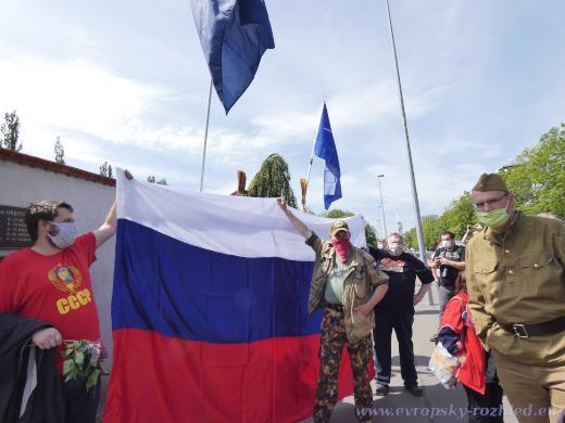 Schování muže s vlajkou NATO za ruskou vlajku.