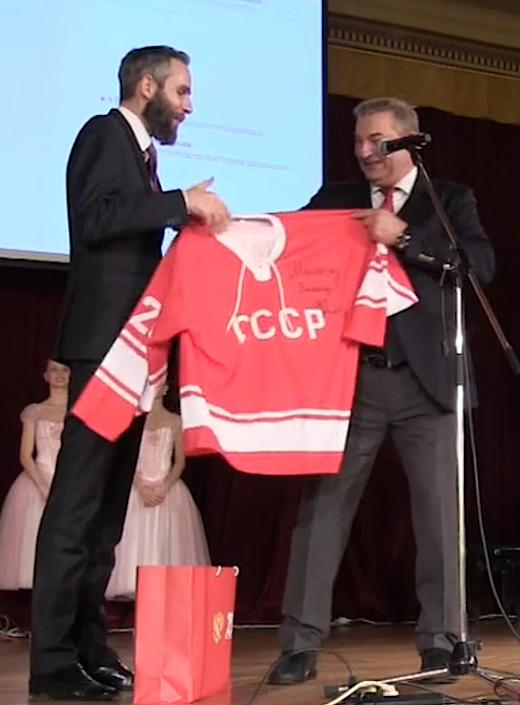 Petr Pirunčík z Kanceláře prezidenta republiky přebírá od prezidenta Ruské hokejové federace Vladislava Treťjaka rudý dres s nápisem SSSR.