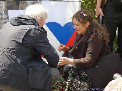Vladimíra Vítová s Karlem Haisem zapalují před papírovým Koněvem svíčku.