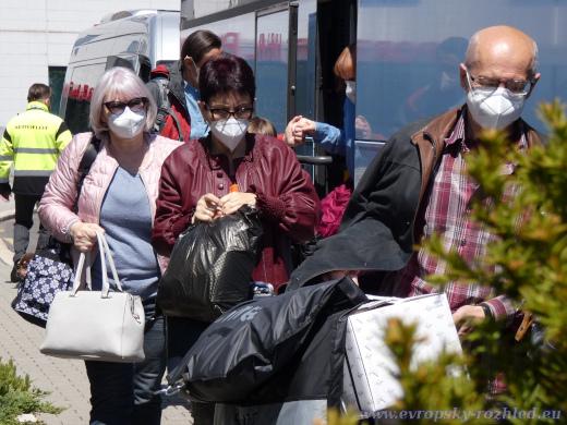 Zaměstnanci ruské ambasády a jejich rodiny vystupují na Terminálu 3 z autobusu.